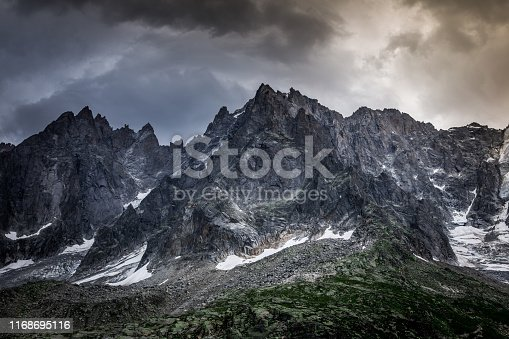 Color image depicting Mont Blanc and the French Alps mountain range still covered in snow even in the height of summer. The mountains are flanked by dense alpine forest as well as a dramatic blue sjy and cloudscape.