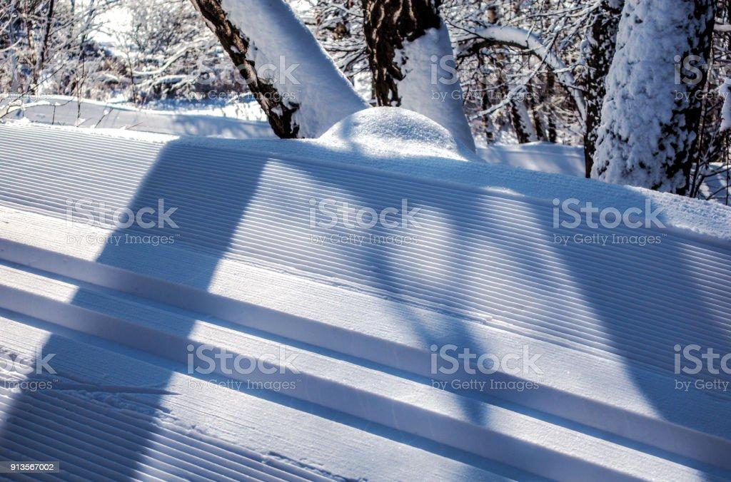Snowcapped road ski tracks closeup stock photo