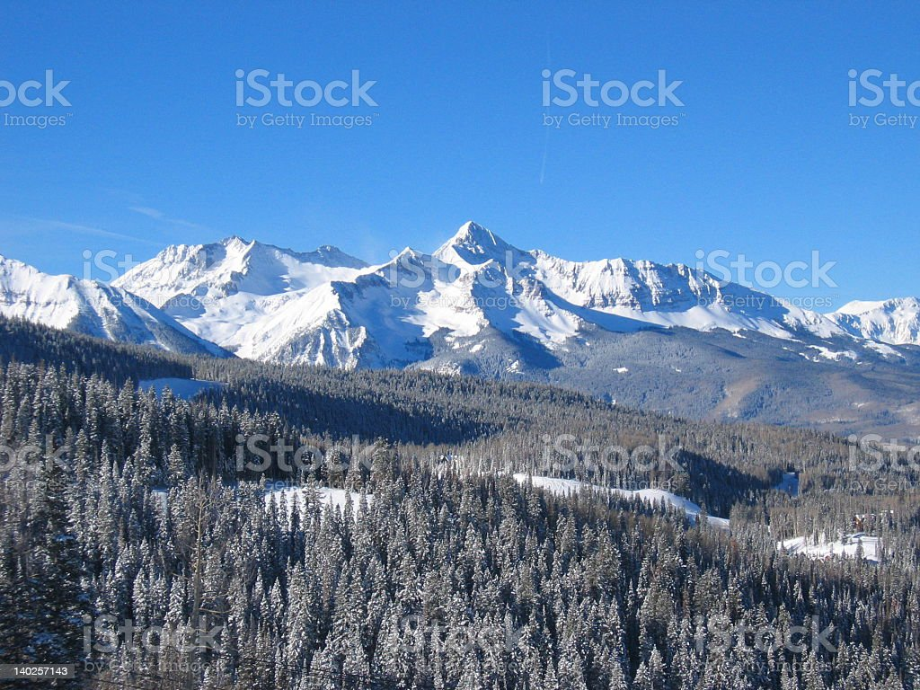Snowcapped Rocky Mountains with bright blue sky stock photo