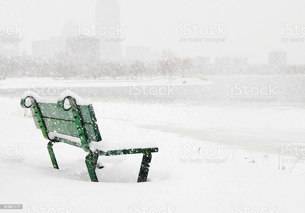 Snow-covered bench on the Charles River in Boston stock photo