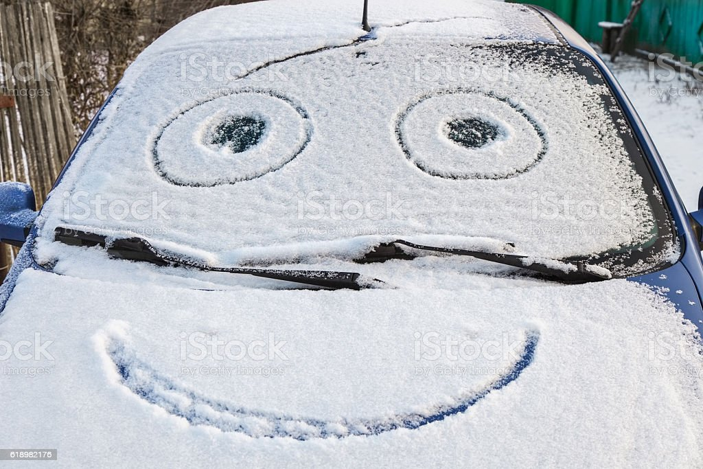 Snow-covered car with smiley stock photo