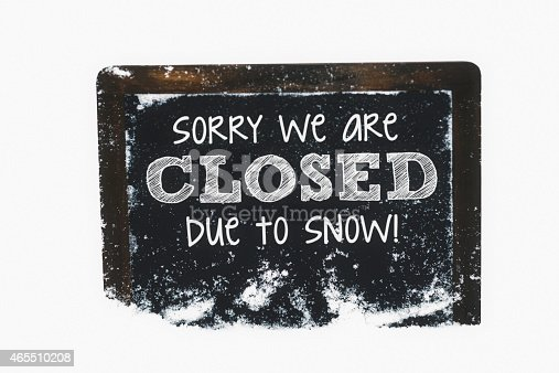 Snow-covered chalkboard reading Closed due to snow. Winter weather concepts.