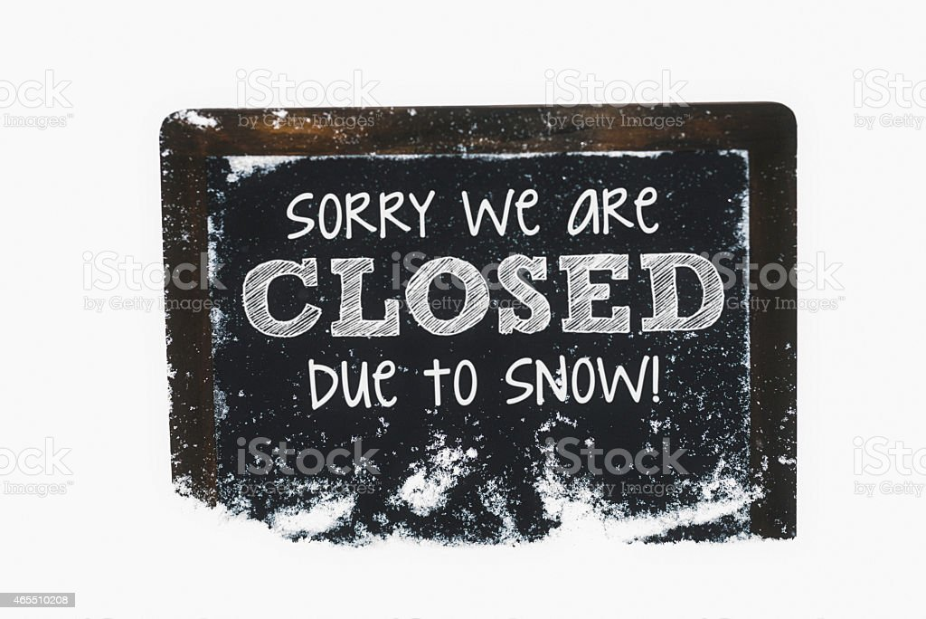 Snow-covered chalkboard reading Closed due to snow. Winter weather concepts. stock photo