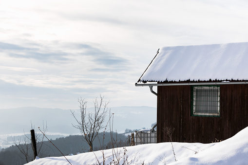 Snow-covered House in the forest in Slovenia on a sunny winter day