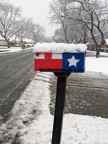A mailbox painted in Texas flag covered with snow beside a Texas road on January 2021. Copy Space.