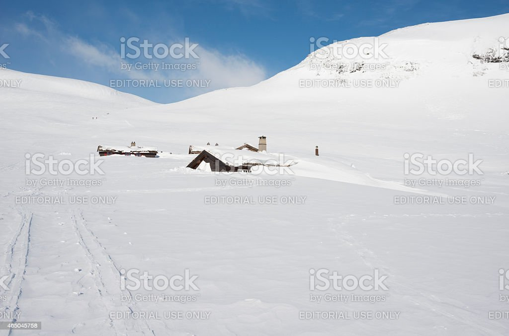 Snow-covered mountain cabins near ski track stock photo