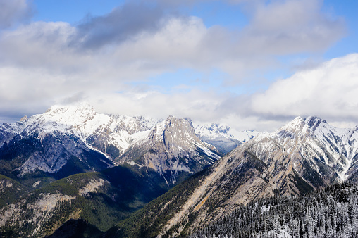 Snow-covered mountains under low clouds, near Banff, Alberta, Canada.