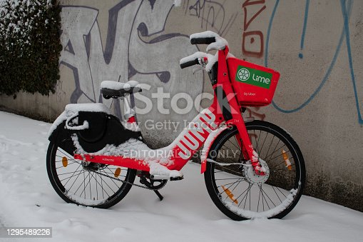 Munich, Germany - January 6, 2021: A snow-covered shared e-bike by JUMP / Lime by Uber parked on a sidewalk in winter, in front of a wall with graffiti.