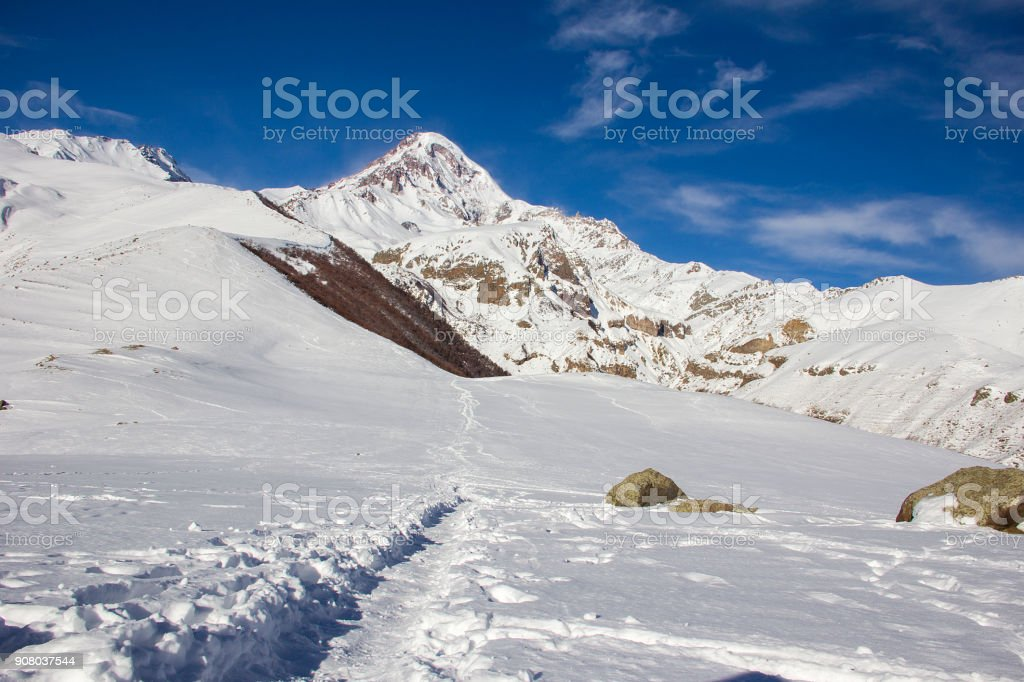Snow-covered peak of Mount Kazbek, footpath, winter landscape. View from the Holy Trinity Church, Gergeti, Georgia stock photo
