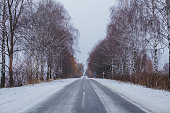 Snow-covered road with birches without foliage. Car on a slippery road. rolled track on first snow. Danger of drifts.