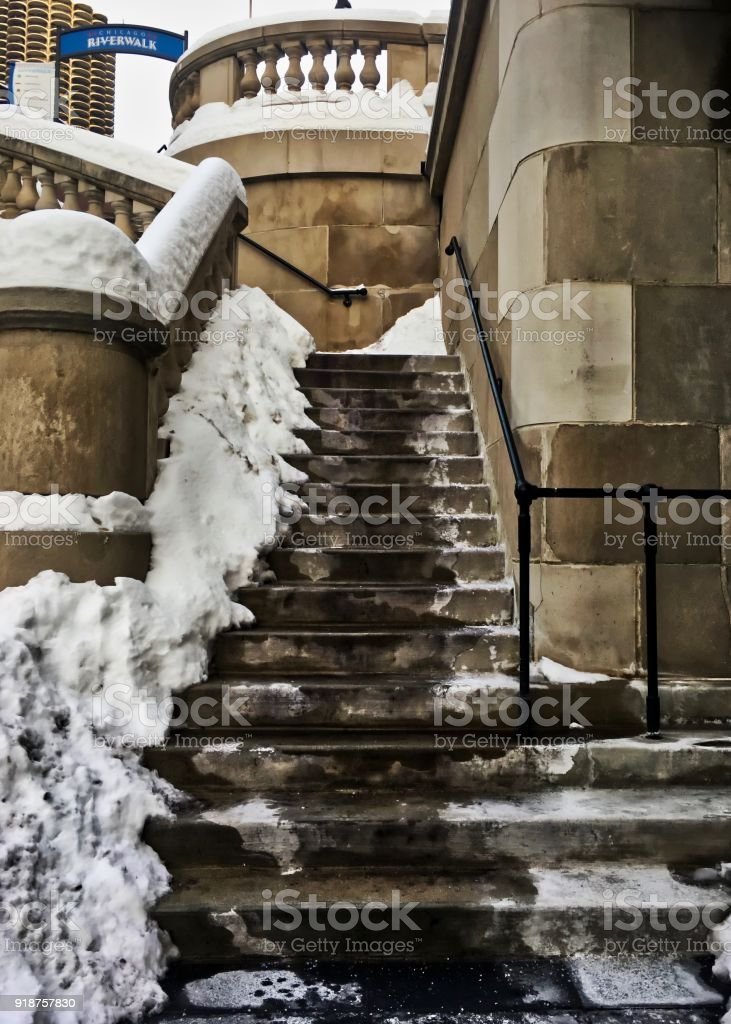 Snow-covered staircase in Chicago Loop during winter, leading upwards and away from the Chicago Riverwalk in the Loop. stock photo