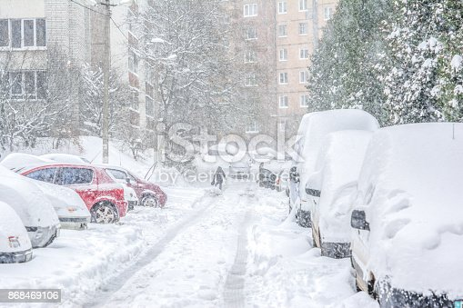 Snow-covered street and cars with a lonely pedestrian. Heavy snowstorm
