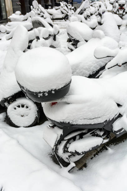 Snow-covered two and three-wheel scooters with top cases parked outdoors in the streets of Paris Snow-covered two and three-wheel scooters with top cases parked outdoors in the streets of Paris. three wheel motorcycle stock pictures, royalty-free photos & images