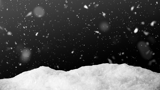 Snow on black background with snowfall. Snowdrift backdrop in the winter night.