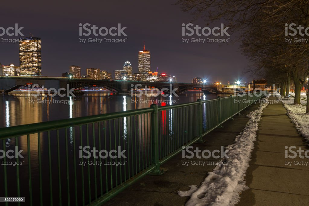 Snowed Cleared Path Next to Green Rail with downtown Boston on the background stock photo