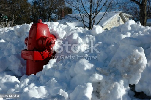 Bright red fire hydrant trapped in a snow bank. Horizontal composition.
