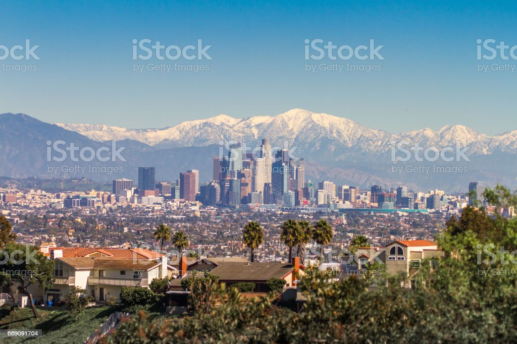 Snowed peaks mountains and downtown Los Angeles cityscape stock photo
