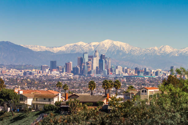 snowed peaks mountains and downtown los angeles cityscape - skyline mountains usa stock photos and pictures
