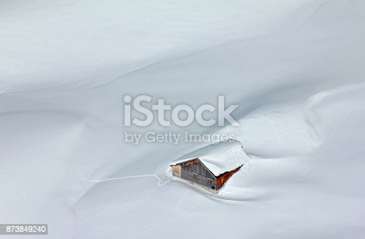 istock Snowed-in mountain hut in the Alps 873849240