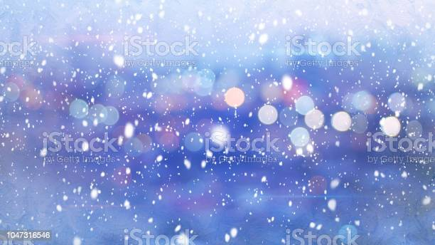 Photo of snowfall and defocused lights evening wintry city