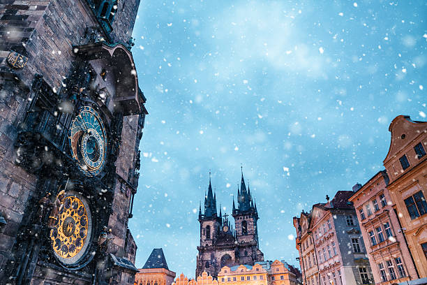 Snowfall On Old Town Square In Prague Astronomical Clock Tower on Old Town Square in Prague (Czech Republic, Europe) on a snowy winter evening. astronomical clock prague stock pictures, royalty-free photos & images