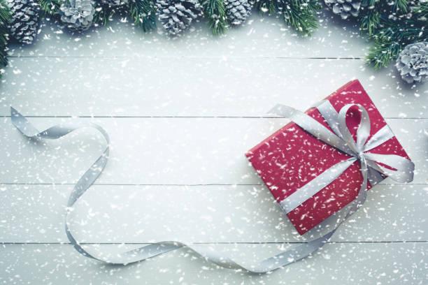 schneefall auf rote geschenke geschenk-box mit grenze kiefer. für weihnachten - günstige weihnachtsgeschenke stock-fotos und bilder