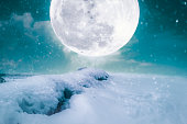 Photo Manipulation. Landscape at snowfall with supermoon. Majestic night with bright full moon on sky. Snow covered the ground in winter season. Serenity nature background. The moon taken with my camera.
