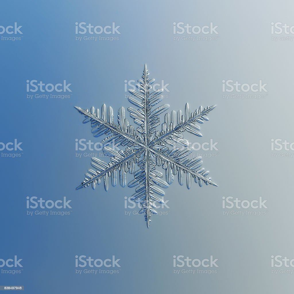Snowflake glittering on smooth gradient background stock photo