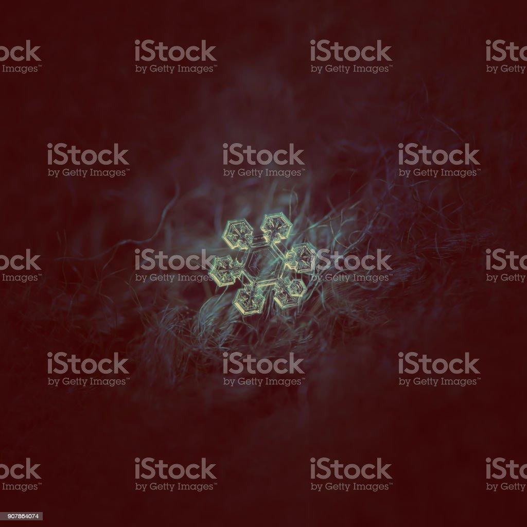Snowflake glowing on dark textured background stock photo