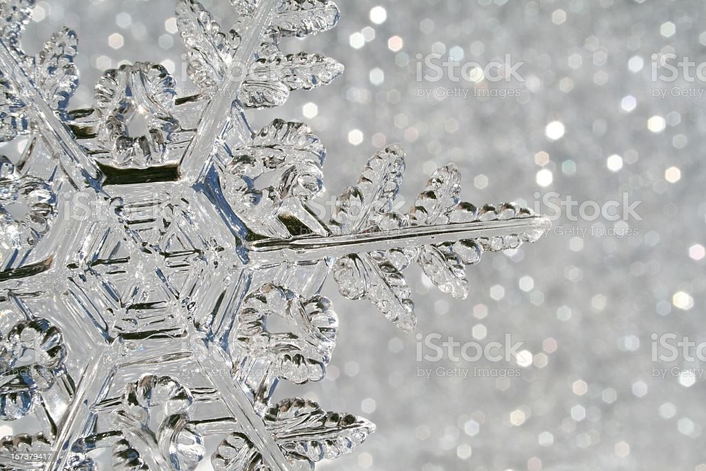 Snowflake macro A glass snowflake Christmas ornament shot in front of a sparkle background that looks like snow glittering.  Since the ornament is made from glass, it looks a little bit 'melty' with soft edges and glittery sparkle. Abstract Stock Photo