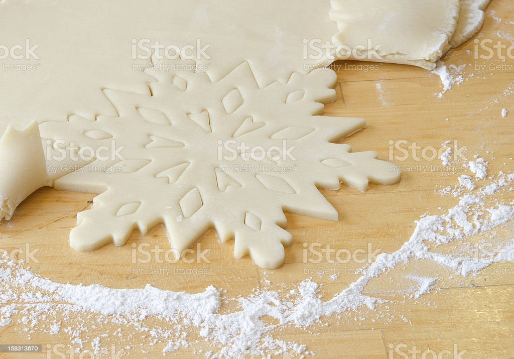Snowflake shape cut from cookie dough royalty-free stock photo