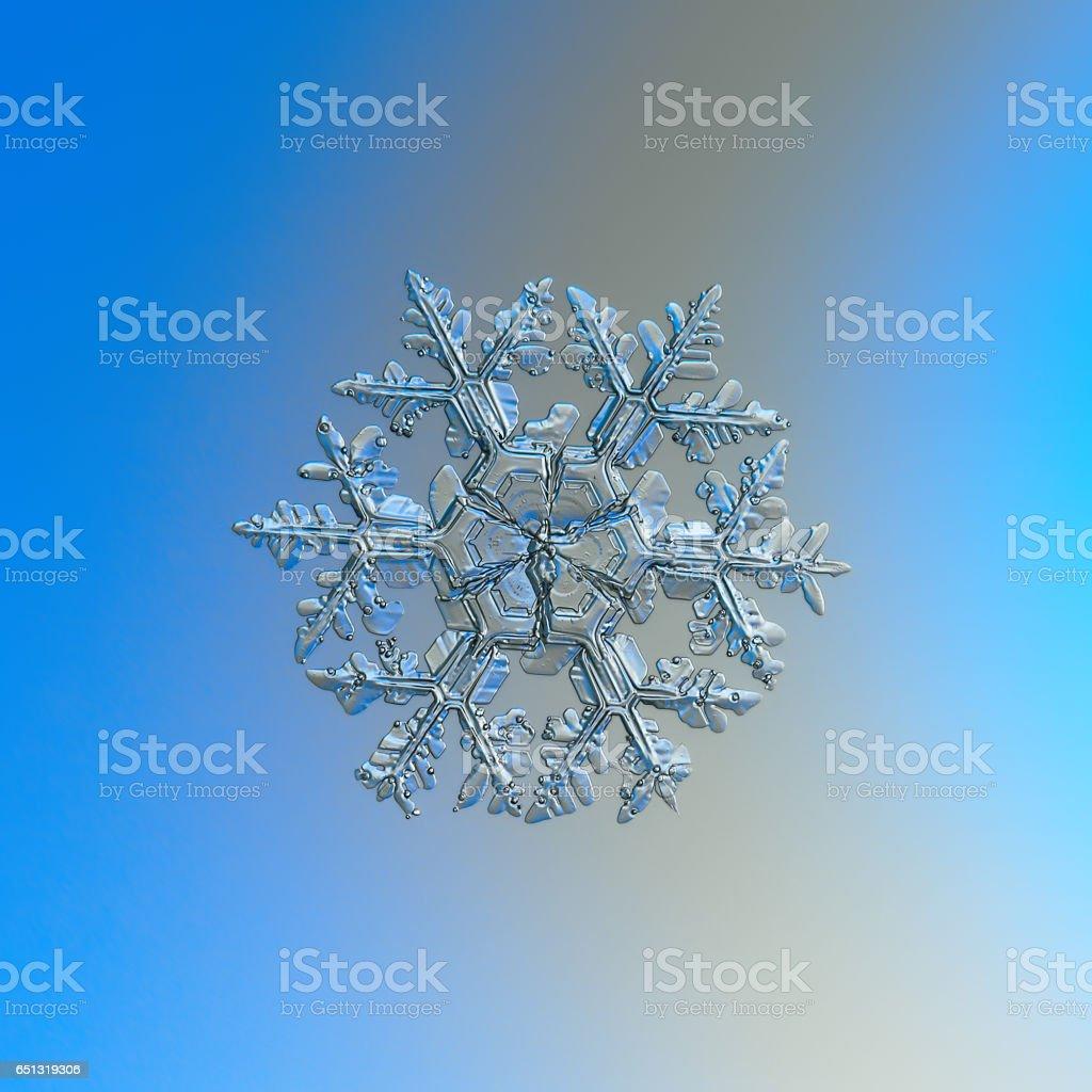 Snowflake sparkling on bright gradient background stock photo