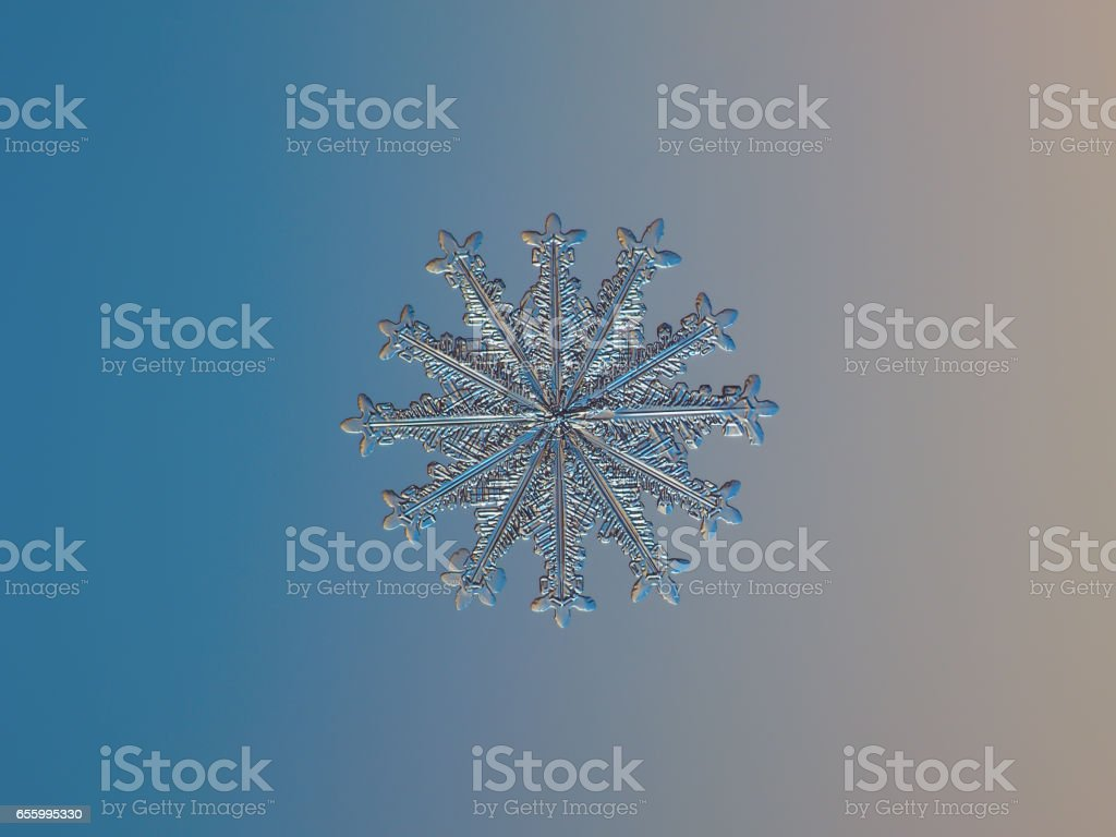 Snowflake with twelve arms sparkle on smooth gradient background stock photo
