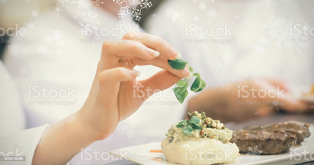 Snowflakes against female chef garnishing a plate with steak stock photo