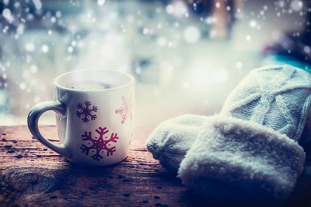 snowflakes mug with hot beverage and mittens on window sill - flocon de neige neige photos et images de collection