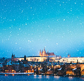 Prague (Czech Republic) with Charles bridge and St. Vitus chatedral on a snowy Christmas evening.