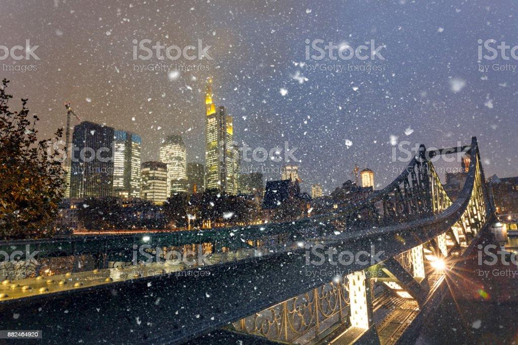 Snowing on Eiserner Steg with the illuminated Frankfurt am Main skyline at dusk stock photo