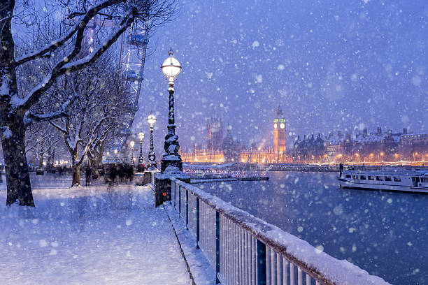Snowing on Jubilee Gardens in London at dusk View of Jubilee Gardens and Westminster Palace during the winter holidays in London. london england stock pictures, royalty-free photos & images