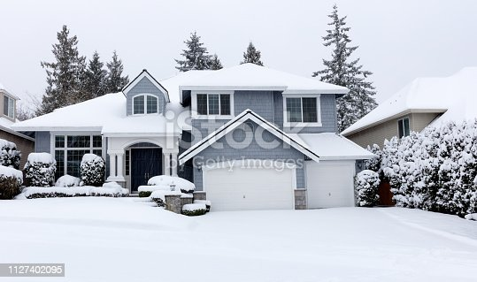 Front view of falling snow with home during rare storm in Pacific Northwest of United States