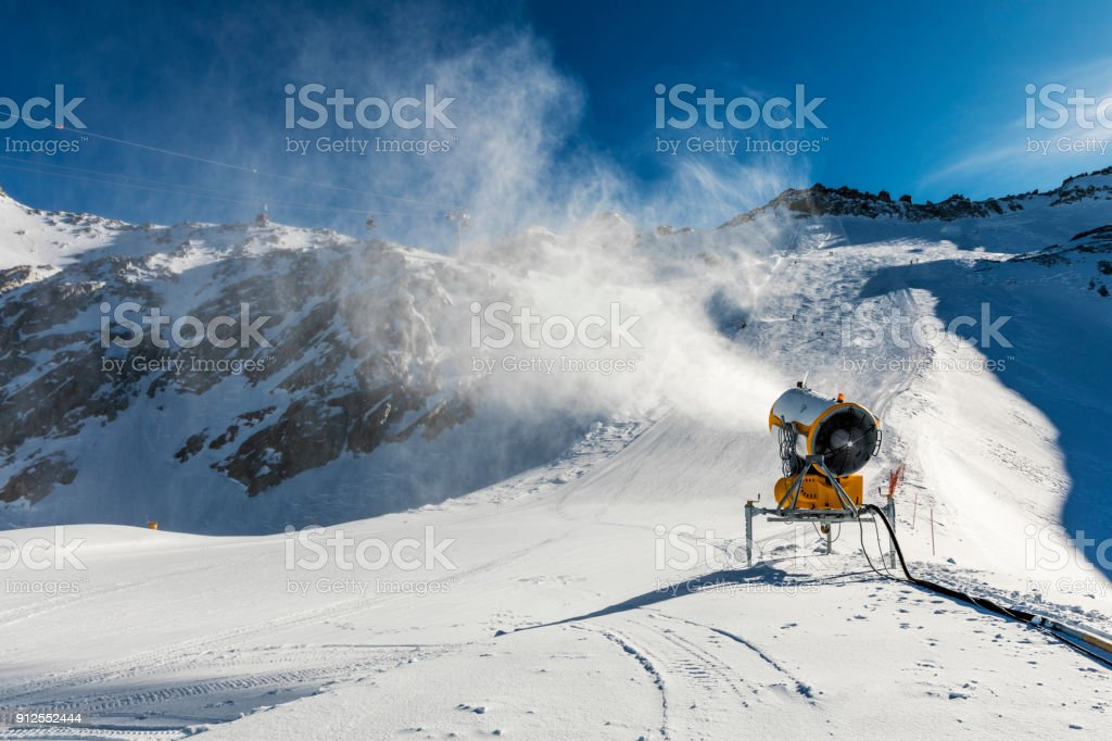 snowmaking - snow cannon working on the slope stock photo