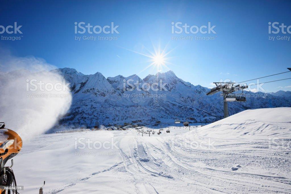 Snowmaking with snow gun Ski slope artificial snowing Ski resort at sunny ski resort Italy Italian Alps Dolomite Amateur Winter Sports stock photo