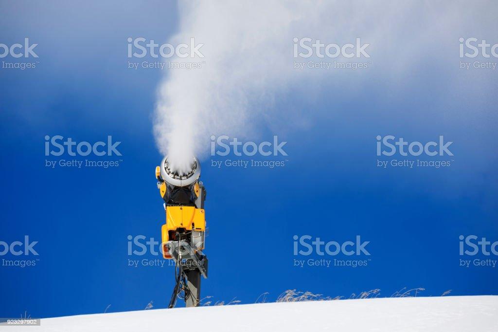 Snowmaking  with snow gun.  Ski slope artificial snowing. Ski resort  with snow cannon - snow making machine. Beautiful winter nature. Fresh snow on the top of  mountains.  High mountain landscape  Ski area. stock photo