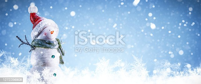 Happy snowman standing in a snowy winter day. Christmas landscape.
