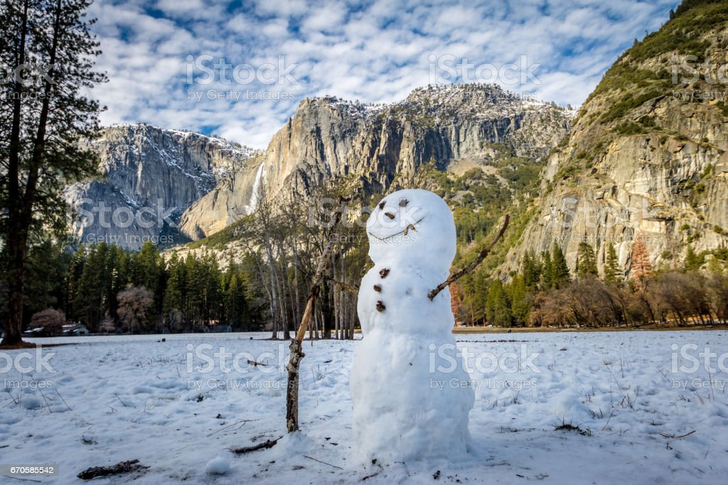 Snowman at Yosemite Valley during winter with Upper Yosemite Falls on background - Yosemite National Park, California, USA stock photo