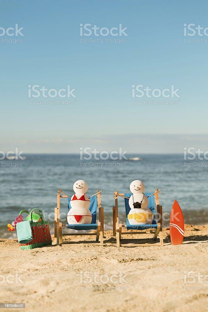 snowman couple relaxing on beach chairs enjoying winter tropical