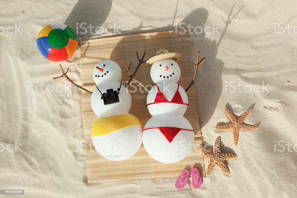 Snowman Couple Winter Vacation Sunbathing in Tropical White Sand Beach stock photo