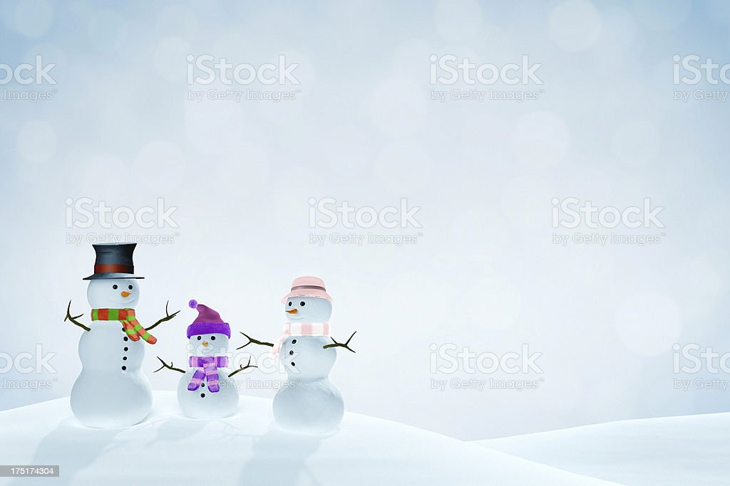 Snowman family in a snowy landscape stock photo