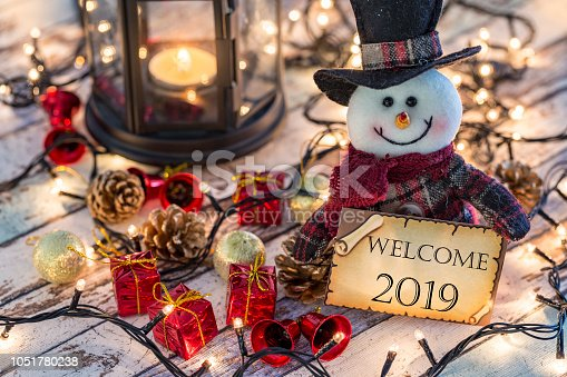 istock Snowman holding greeting card for new year or christmas with christmas decorations and lights 1051780238