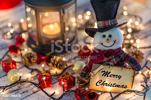 istock Snowman holding greeting card for new year or christmas with christmas decorations and lights 1051788378