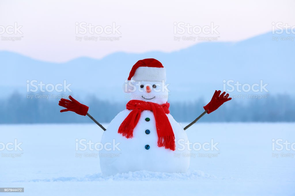 1a9b54766295d Snowman in red hat and scarf. Christmas scenery. High mountains at the  background. Ground covered by snow. Nice cold winter day. - Stock image .